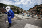 A Brazilian policeman dressed as Santa Claus in Rio de Janeiro's military police colours, arrives for a Christmas party at Macacos slum (Reuters)