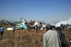 People gather at the wreckage of a Air Bagan Fokker-100 passenger jet that crashed in Heho (Reuters)