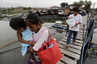 Filipino residents carrying babies cross a makeshift bridge at a fishing village in Paranaque city, south of Manila (AAP)