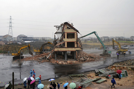 Excavators demolish the house standing alone in the middle of a newly built road in Wenling, China (Reuters)
