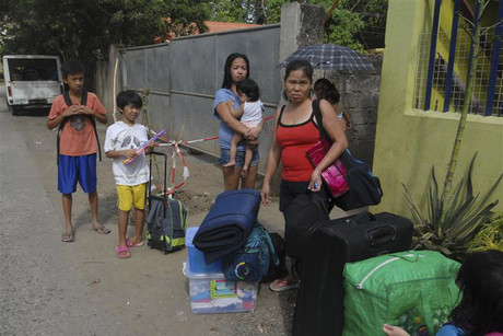 Residents wait for a truck to transport them into an evacuation center as local officials ordered enforced evacuation ahead of Typhoon Bopha in southern Philippines (Reuters)