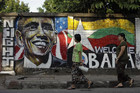 Women walk pass a wall with graffiti welcoming US President Barack Obama on a street side in Yangon (Reuters)