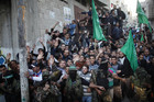 Palestinian brigades hold back the crowd as Mashaal visits a detroyed house in Gaza  (Reuters)