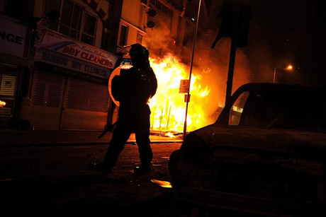 A riot policeman advances past a burning building in Croydon, south London, during the riots in 2011 (Reuters)