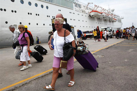 Passengers walk with their luggage after alighting from the Costa Allegra cruise ship at Mahe port in the Seychelles (Reuters)