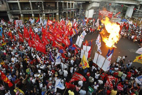 Protesters burn an effigy of President Aquino during a Labour Day march in Manila (Reuters)