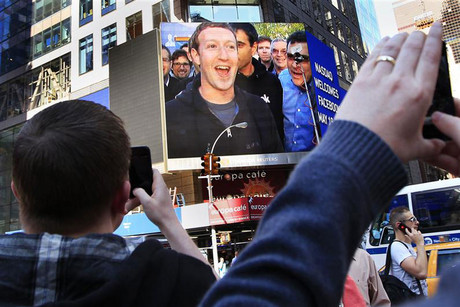 Mark Zuckerberg applauds with Facebook employees as stock begins trading (Reuters)
