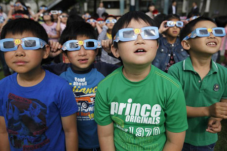 School children watch the annular eclipse with solar viewers at Hirai Daini Elementary School in Tokyo (Reuters)