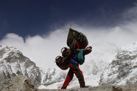 A Nepalese porter walks with his load from Everest base camp in Nepal (Reuters)