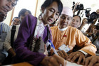 Myanmar pro-democracy leader Aung San Suu Kyi signs the register as she arrives at the lower house of parliament (Reuters)