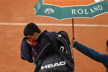 Novak Djokovic of Serbia leaves the court as rain stops the play during his men's singles final match against Nadal of Spain at the French Open tennis tournament at the Roland Garros stadium in Paris (Reuters)