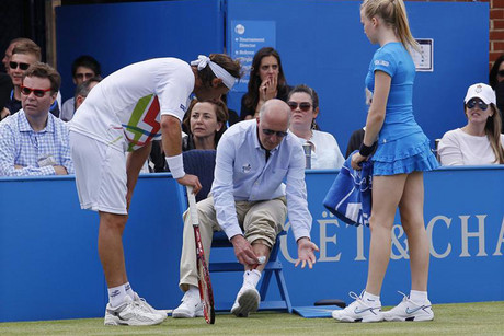 Nalbandian of Argentina looks as a line judge shows his injury after he kicked hoarding during his men's singles final match (Reuters)