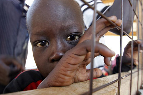 A refugee child from South Sudan stands at a registration centre (Reuters)
