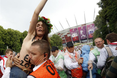 A topless women's rights group FEMEN activist is carried away by a security officer as she protests against Euro 2012 (Reuters)