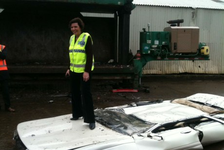 Anne Tolley poses atop the first car crushed under the law