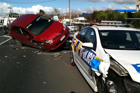 A car ended up on top of another car with the police car damaged