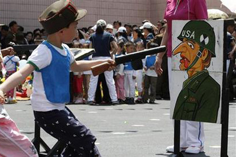 A child points a toy gun at a picture of a US soldier (Photo: Reuters)