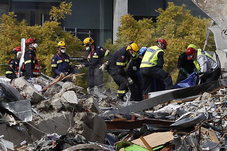Rescue workers recover a body from the rubble of the CTV building in Christchurch (Reuters)