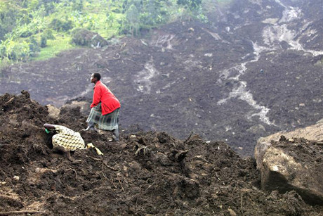 A woman searches for her missing relatives in a pile of soil  (Photo: Reuters)