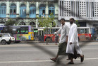 Muslim men walk near Sule Pagoda in Yangon (Reuters)
