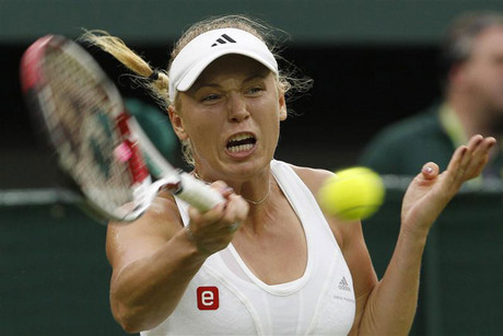 Caroline Wozniacki of Denmark hits a return to Tamira Paszek of Austria during their women's singles tennis match at the Wimbledon tennis championships in London (Reuters)