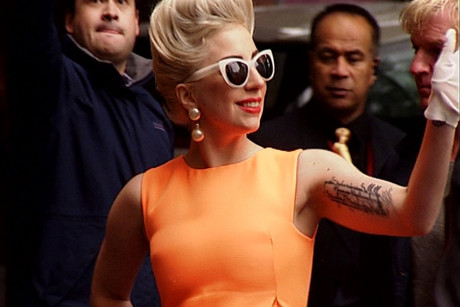 Lady Gaga waves to fans outside the Stamford Plaza