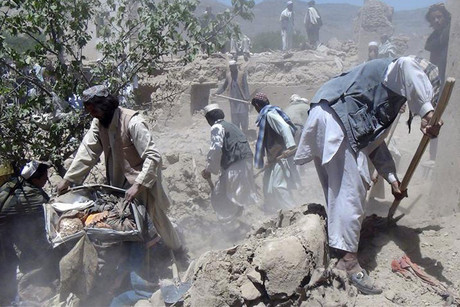 Afghan men search for the bodies of people killed in a NATO airstrike in Logar province (Reuters)