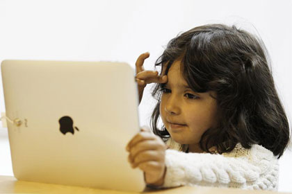 A girl uses an iPad (Reuters)