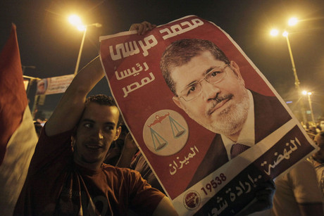 A supporter of Egypt's first Islamist President Mohammed Morsi cheers with a poster of him at Tahrir Square (Reuters)
