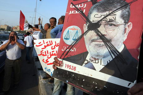 Egyptian protesters with a sign reading in arabic 'no to Muslim Brotherhood' in Nasr City, Cairo (AAP)