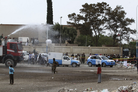 Policemen spray water to disperse a crowd of people at the site of the suicide bombing (Reuters)