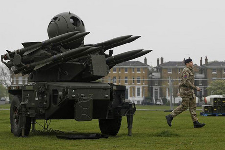A soldier runs past a Rapier missile defence battery which will be placed on residential housing rooftops to help guard the Olympic Games (Reuters)