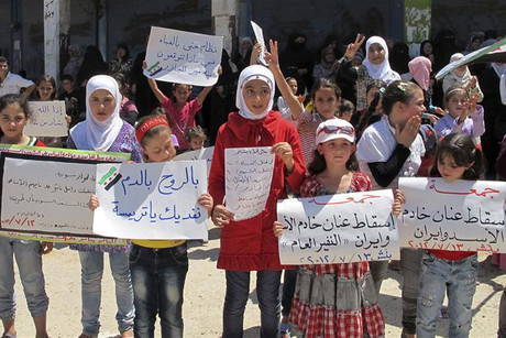 Girls hold signs and shout slogans against Syria's President Bashar al-Assad, in Bennish (Reuters)