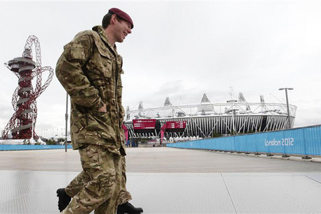 Two soldiers walk through the Olympic Park with the Olympic Stadium behind them in Stratford, east London (Reuters)