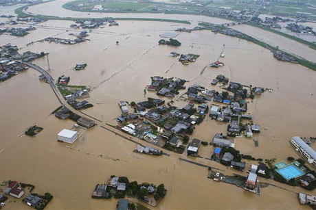 An aerial view shows flooded residential area after a bank of the Yabegawa river collapsed caused by heavy rains in Yanagawa, Japan (Reuters)