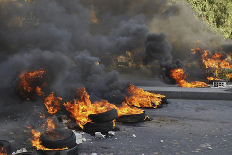 Demonstrators burn tyres to block a road during a protest against Syria's President Bashar al-Assad in Jubar near Damascus (Reuters)