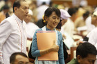 Burma pro-democracy leader Suu Kyi walks among Members of Parliament in a meeting room as she attends a parliamentary meeting at the Lower House of Parliament in Naypyitaw (Reuters/Soe Zeya Tun)