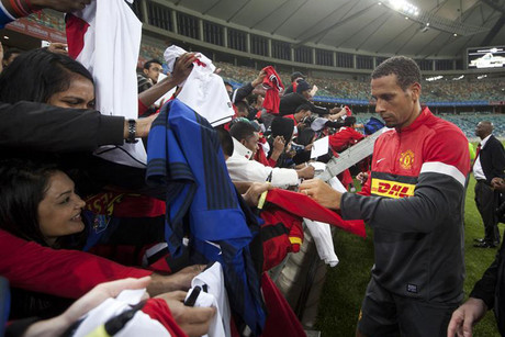 Manchester United's Ferdinand signs fans shirts after training  