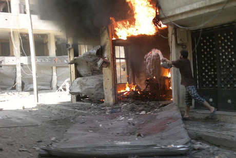 A fire burns after a shelling at Juret al-Shayah in Homs city (Reuters)