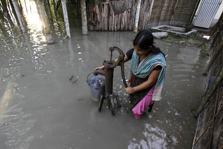 A flood-affected girl uses a submerged hand-pump to fetch drinking water at Dhuhibala village in the northeastern Indian state of Assam (Reuters)