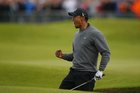 Tiger Woods celebrates after chipping in from the bunker