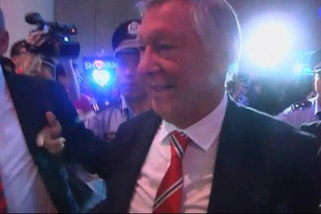 Sir Alex Ferguson is shuffled through the crowd in China