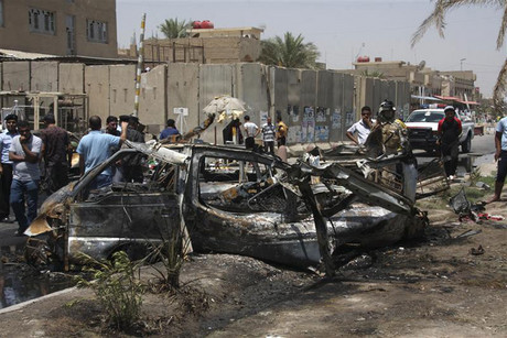Residents gather at the site of a car bomb attack in Sadr City, northeastern Baghdad (Reuters)