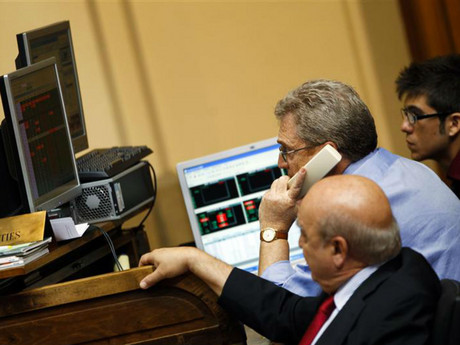A trader talks on the phone next to computer screens at the Madrid Bourse (Reuters)