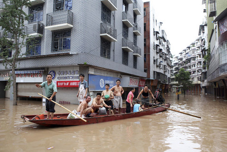 Rescuers row a boat carrying residents to a safer area along a flooded street in Yongchuan district, Chongqing (Reuters)