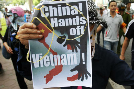 A protester holds an anti-China placard as she marches in Hanoi (Reuters)
