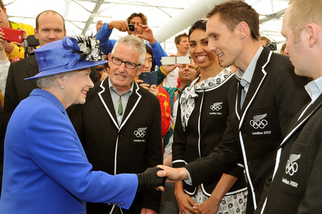 Queen Elizabeth II meets the Nick Willis of New Zealand, as she and the Duke of Edinburgh tour the Athletes Village dinning hall in Stratford east London (AAP)
