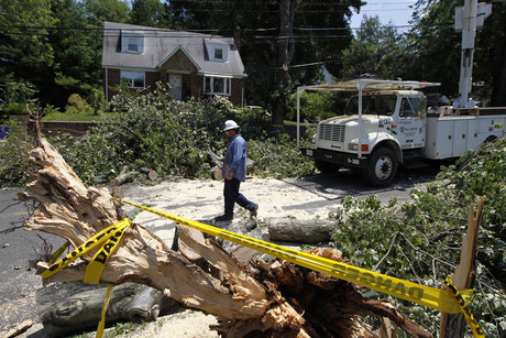 An electrical worker walks down a street where a fallen tree had cut overhead power lines, during emergency repairs in Wheaton (Reuters)