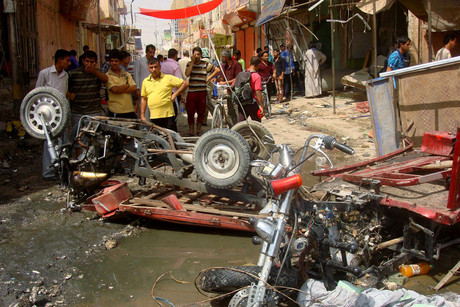 Residents look at damaged vehicles at the site of a bomb attack in a market in Diwaniya (Reuters)