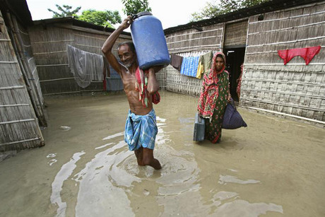 Flood-affected people carry their belongings in front of their flooded huts as they move to safer places in Marigaon district (Reuters)